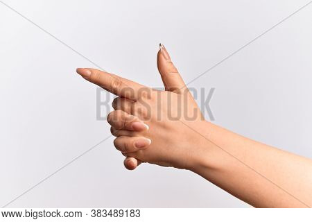 Hand of caucasian young woman gesturing fire gun weapon with fingers together, aiming shoot symbol