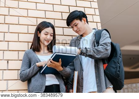 Students Stand To Read A Book Together On The Campus. Education Concept.