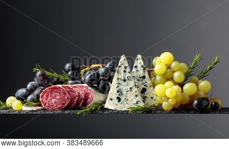 Blue Cheese, Dry-cured Sausage, Grapes, And Rosemary On A Black Background.  Copy Space.