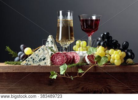 Wine And Snacks On An Old Wooden Table. Glasses Of Wine, Blue Cheese, Dry-cured Sausage, Grapes, And