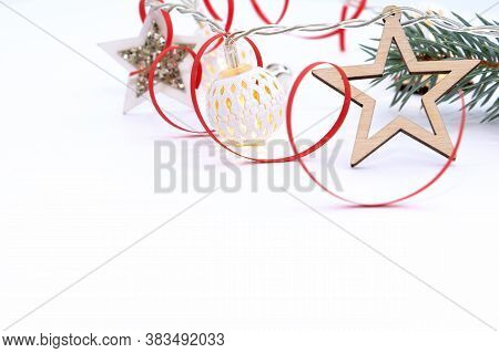 Christmas Composition Of Fir Branches, Wooden Stars, Garlands Of White Luminous Balls And Red Ribbon