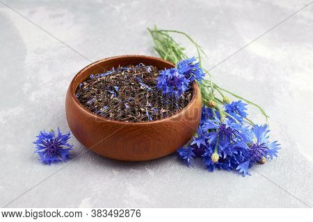 Blend Of Black Tea, Cornflowers Petals In Wooden Bowl With Fresh Blue Cornflowers