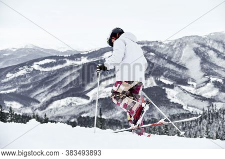 Back View Of Alpine Skier In Jacket And Helmet Skiing In Mountains. Man Freerider With Ski Sticks Wa