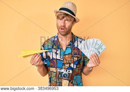 Young blond man wearing summer style holding paper plane and dollars in shock face, looking skeptical and sarcastic, surprised with open mouth