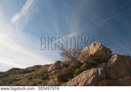 Rocks In The Foreground And Contrails Of Airplanes In The Sky.