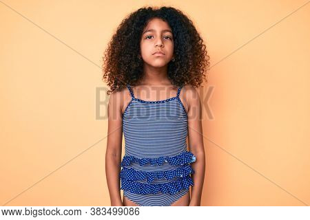 African american child with curly hair wearing swimwear with serious expression on face. simple and natural looking at the camera.