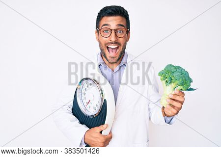 Young hispanic man as nutritionist doctor holding weighing machine and broccoli smiling and laughing hard out loud because funny crazy joke.