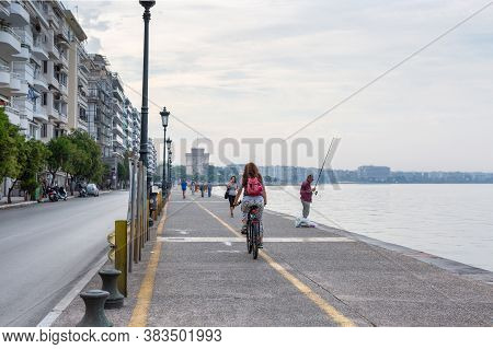 Thessaloniki, Greece - September 12, 2016: Girl With Red Backpack Riding Bicycle Along The Seafront