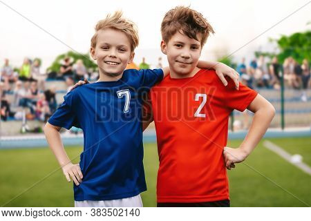 Two Happy Smiling Boys In Sports Team Standing On Grass Pitch. Kids Making Sports Activity Outdoor.
