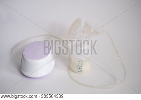 The Electric Breast Pump Is On The Table In The Kitchen. Breast Pump With Milk. Give Expressed Breas