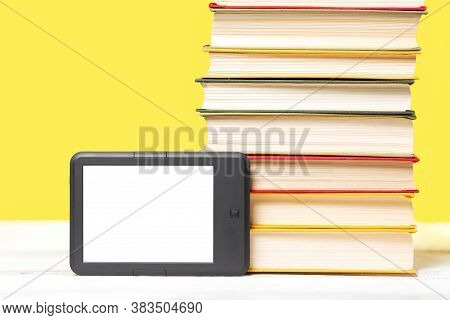 E-learning. E-book Reader And A Stack Of Books On A Yellow Background. Mock Up. Copy Space. Concept