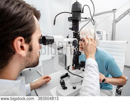 Experienced Doctor Checks The Eyesight Of An Elderly Woman. Modern Clinic For Checking And Treating