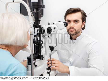 Optometrist Doctor Using A Binocular Slit-lamp Examines The Eye Of An Elderly Woman Patient. Aged Pe