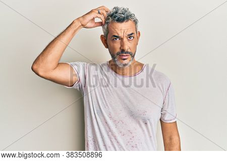 Middle age grey-haired man wearing casual clothes confuse and wonder about question. uncertain with doubt, thinking with hand on head. pensive concept.