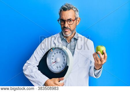 Middle age grey-haired man as nutritionist doctor holding weighing machine and green apple clueless and confused expression. doubt concept.