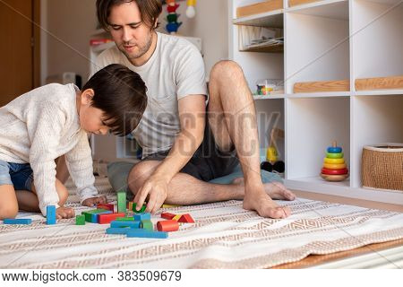 Kid And His Father Playing At Home With Wood Building Blocks. Homeschooling. Stay At Home. Family Ti