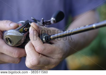 Close-up Of A Male Hand With A Fishing Rod And A Baitcasting Reel. A Caucasian Man Sips A Yellow Bra