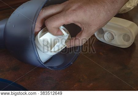 A Male Hand Installs A New Tap Water Purification Cartridge Into A Jug. The Old Cartridge Is Next To