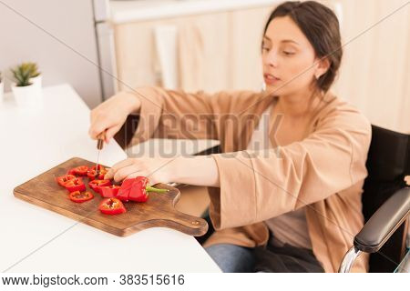 Woman With Legs Paralysis In Wheelchair Cutting Red Pepper On Slicing Board. Disabled Paralyzed Hand