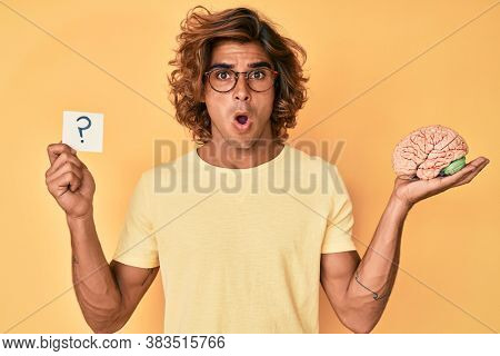 Young hispanic man holding brain and question mark in shock face, looking skeptical and sarcastic, surprised with open mouth