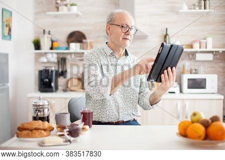 Happy Elderly Person With Portable Tablet Pc In Kitchen During Breakfast. Senior Person With Tablet