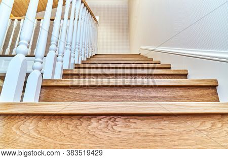Steps Of A Wooden Staircase With White Balusters. Bottom View