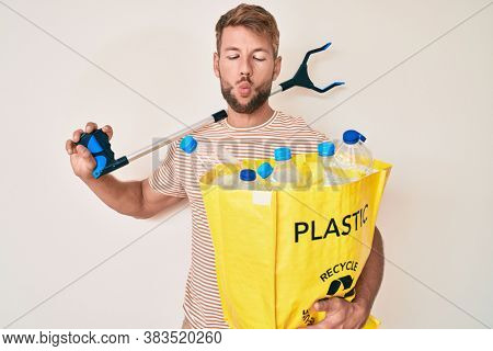 Young caucasian man holding recycling bag with plastic bottles and waste picker making fish face with mouth and squinting eyes, crazy and comical.