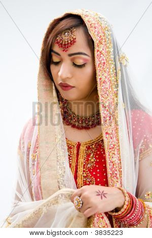 Elegant Bengali bride arranging veil looking down isolated poster