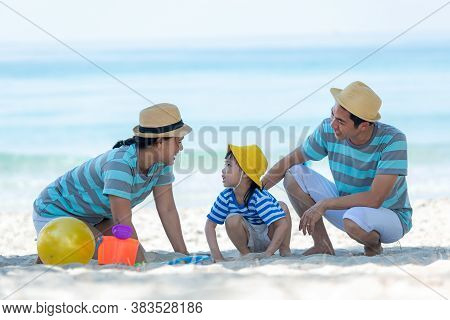 Asian Happy Family Have Fun On The Beach.  Traveling Backpack For Travel In Vacations For Leisure An