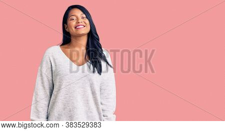 Hispanic woman with long hair wearing casual clothes with a happy and cool smile on face. lucky person.