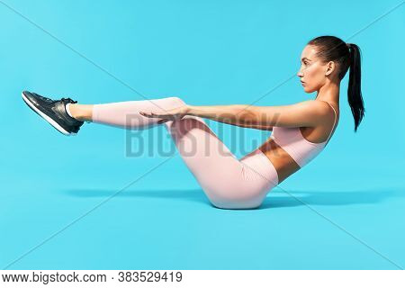 Beautiful Young Woman In Pink Sportswear Doing Fitness Exercise Sit-ups, Abs. On Blue Background