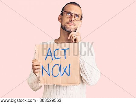 Young handsome man holding act now banner serious face thinking about question with hand on chin, thoughtful about confusing idea