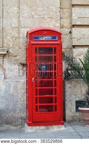 Red Telephone Booth Next To The Wall Of An Traditional House In The Old Town Of M'dina ,malta, Europ