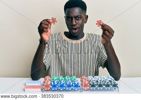 Young african american man playing poker holding casino chips in shock face, looking skeptical and sarcastic, surprised with open mouth