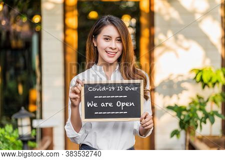 Asian Partner Small Business Owner Hands Holding And Showing The Chalkboard With Wording Covid-19 Is