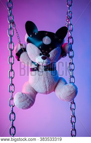 Toy Bear Dressed In Leather Belts Harness Accessory For Bdsm Games On A Dark Background In Neon Ligh