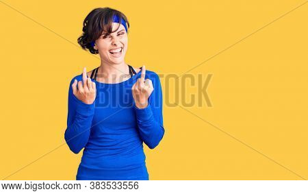 Beautiful young woman with short hair wearing training workout clothes showing middle finger  bad expression, provocation and rude attitude. screaming excited
