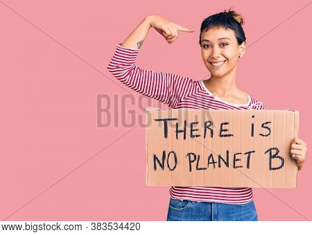 Young woman holding there is no planet b banner pointing finger to one self smiling happy and proud