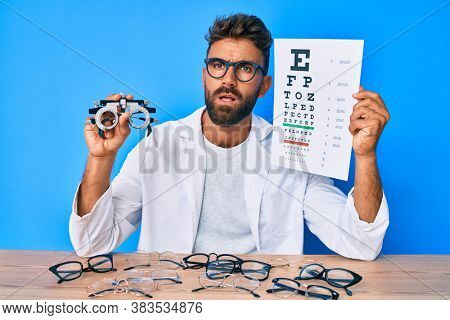 Young hispanic man with optometry glasses and paper with letters in shock face, looking skeptical and sarcastic, surprised with open mouth