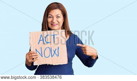 Middle age latin woman holding act now banner smiling happy pointing with hand and finger
