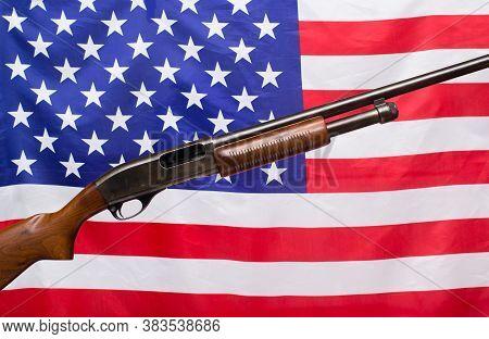 Shotgun And American Flag Symbolizing Gun Control And Rights