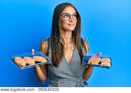 Young hispanic woman holding take away food smiling looking to the side and staring away thinking.