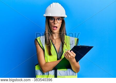Young hispanic woman wearing safety helmet holding clipboard in shock face, looking skeptical and sarcastic, surprised with open mouth
