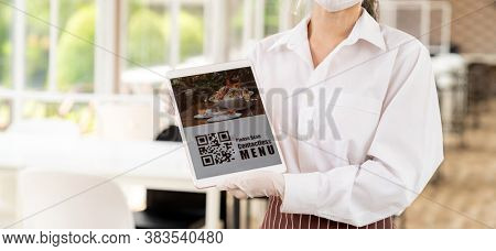Panorama close up waitress with face mask and face shield hold digital tablet with QR code for customer to scan for online contactless menu. QR Code is text