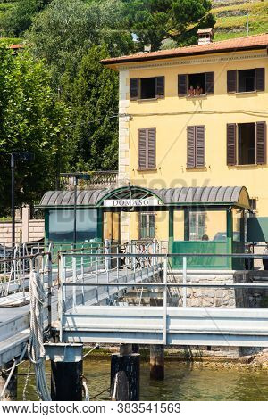Domaso. Lake Como. Italy - July 21, 2019: Ferry Pier in the Commune of Domaso. Lombardy. Signboard with Name of the City.