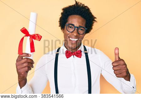 Handsome african american nerd man with afro hair holding graduate degree diploma smiling happy and positive, thumb up doing excellent and approval sign