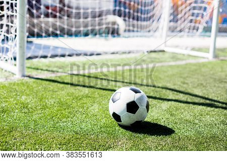 Soccer Ball With Sunlight And Shadow On Green Field In Front Of Goal Post.