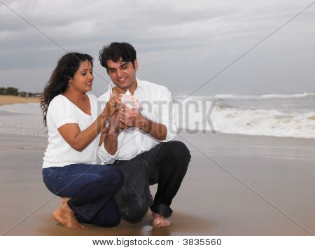 Asian Couple In The Beach Looking At A Conch