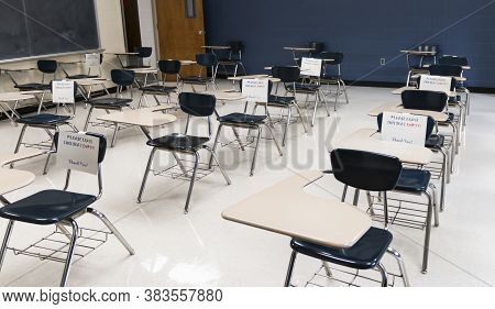 Desks In A High School Classroom Have Sign Reading Fo Not Sit Leave Empty To Help In Makeing The Roo