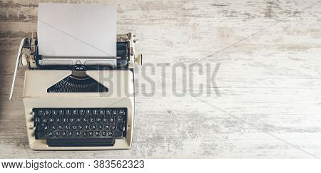 Typewriter On The Grey Wooden Table Background